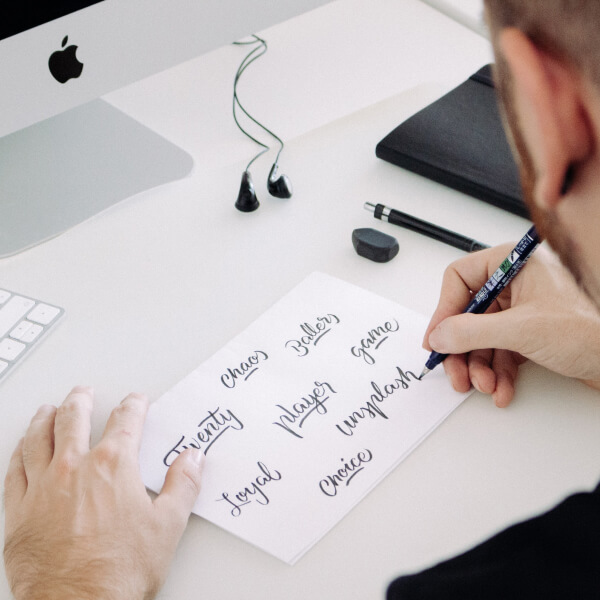 A decorative photo of a person writing on a piece of paper.